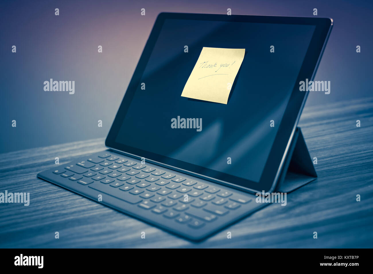 Thank you note on digital tablet screen standing at office desk - Stock Image