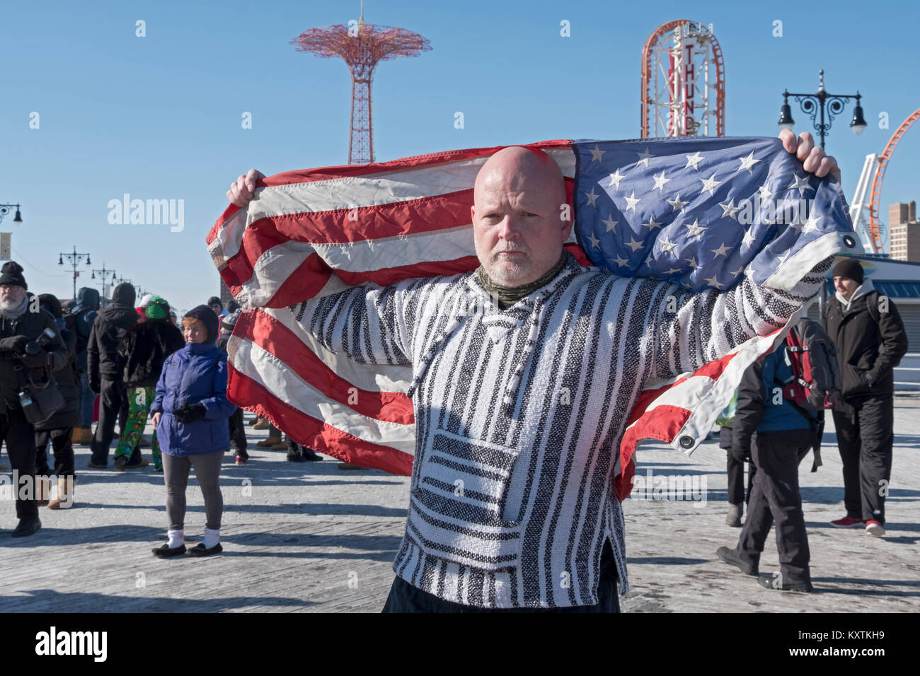 A man with an American flag on the boardwalk prior to the 114th Polar Bear Club New Year's Day swim. - Stock Image