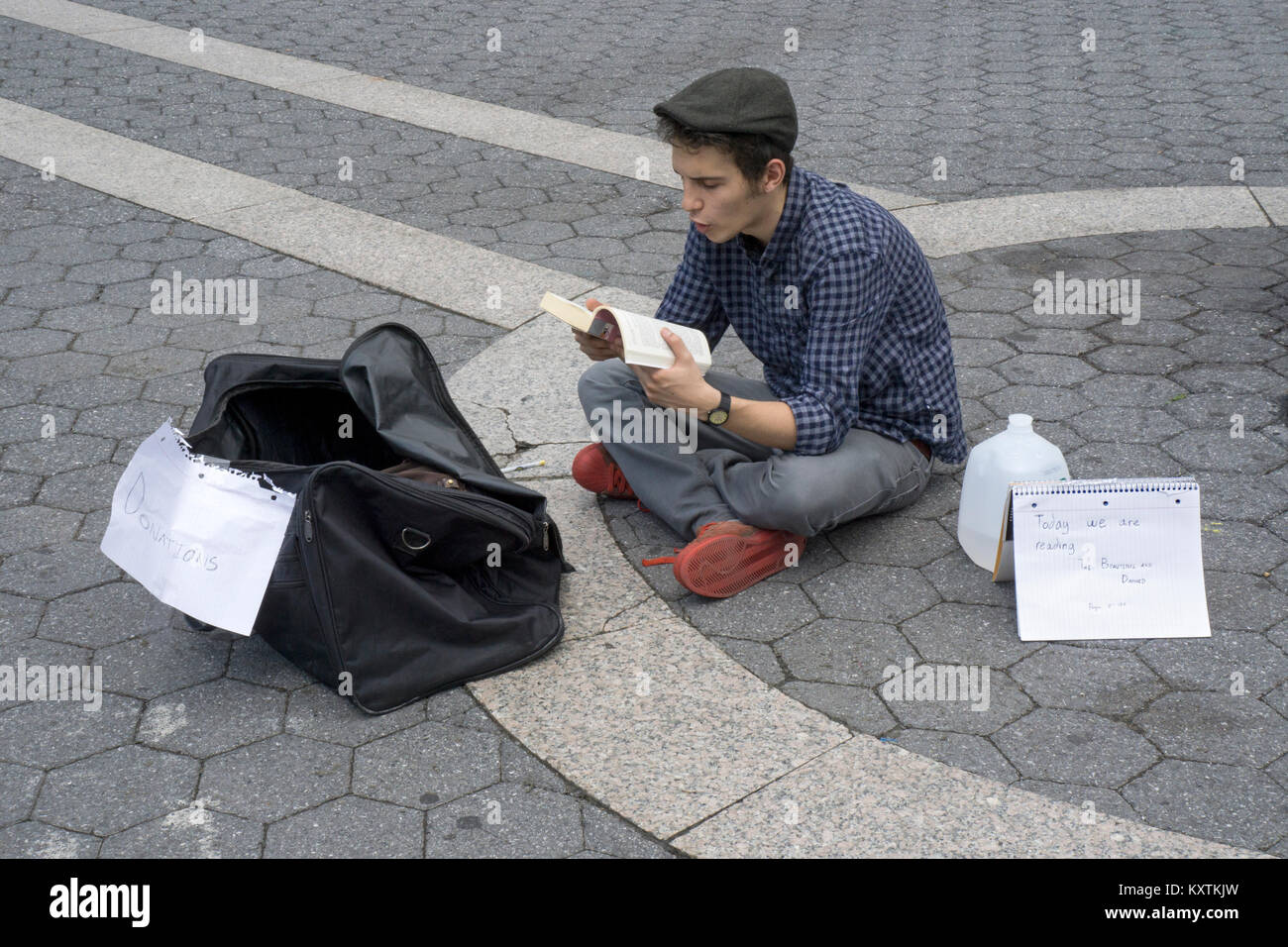 A young man soliciting donations by reading aloud from F. Scott Fitzgerald's novel The Beautiful and the Damned. - Stock Image