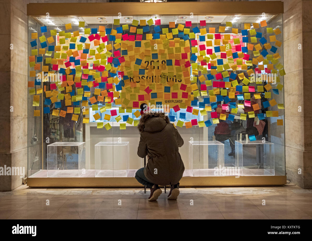 A woman writing her New Years '18 resolution on a stickie note & posting it on the window of the gift shop - Stock Image