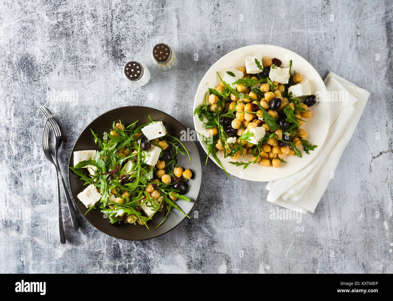two plates of vegetable salad with chickpeas, arugula, feta cheese or tofu and black olives on a natural stone background. Stock Photo