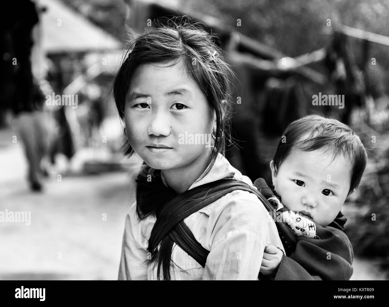 Little girl carrying her brother behind her shoulders till her mother come back from work, Vietnam - Stock Image