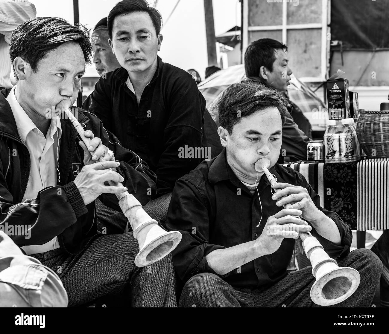 Men playing traditional music instrument in Sapa market, Vietnam - Stock Image
