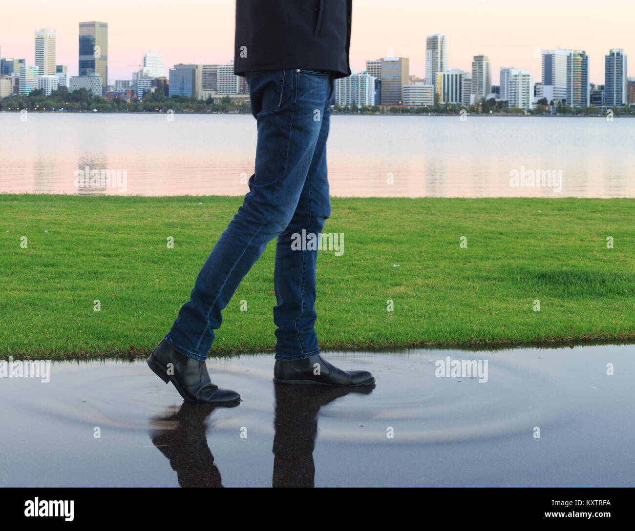 A man wearing boots walking through a puddle - Stock Image