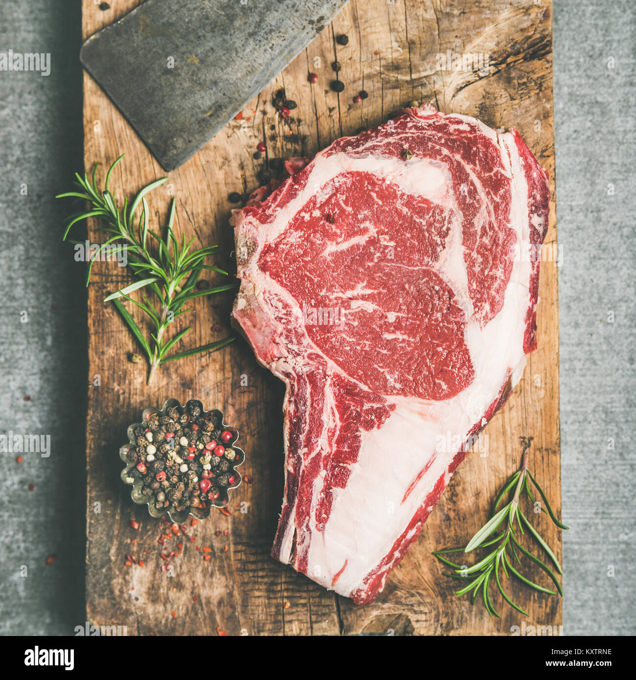 Raw prime beef meat steak rib-eye and chopping knife, flat-lay - Stock Image