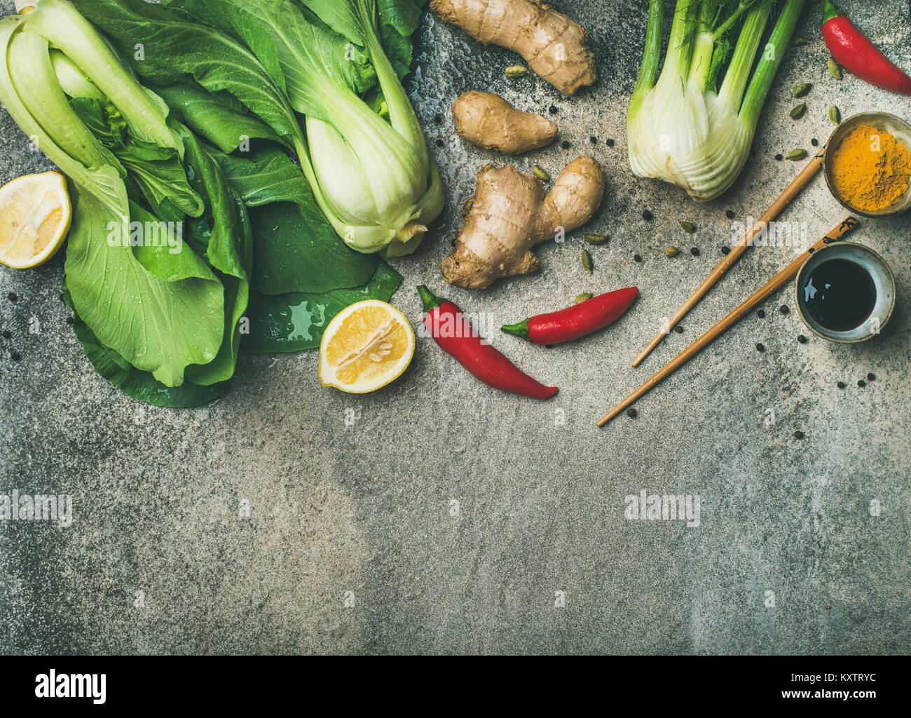 Flat-lay of Asian cuisine ingredients over concrete background, copy space - Stock Image