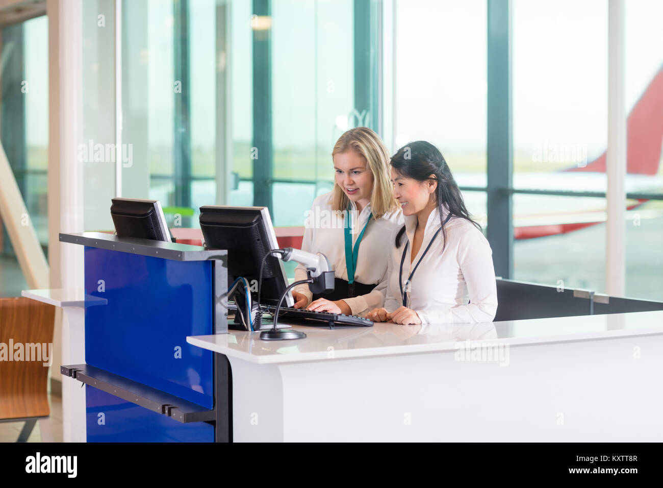 Multiethnic receptionists using computer at counter in airport - Stock Image