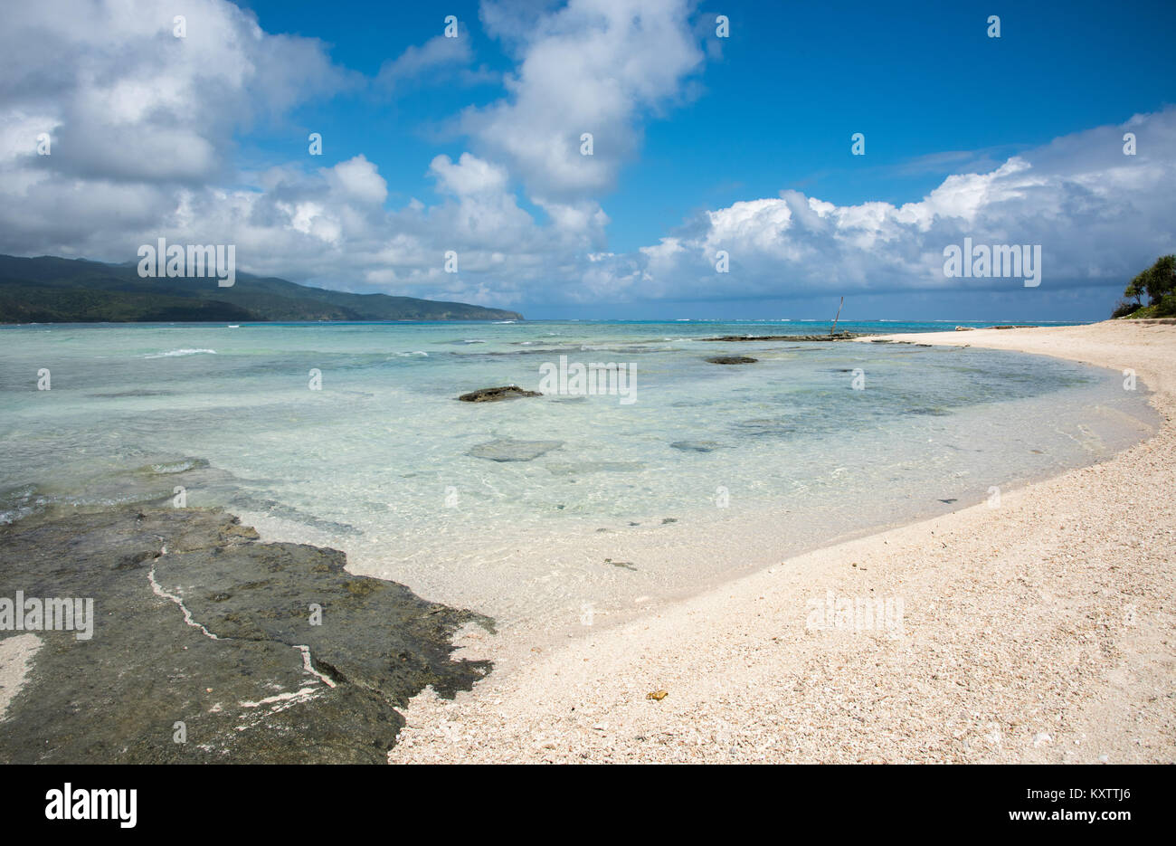Peaceful beach with mountain view, coastal rock and seascape at Mystery Island, Vanuatu - Stock Image