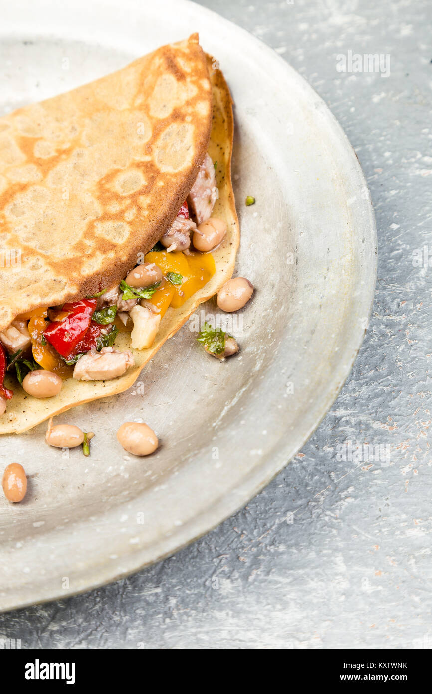 Savoury Buckwheat Pancake with White Beans, Red and Yellow Bell Pepper, Parsley and Chicken. Mexican Quesadilla. - Stock Image