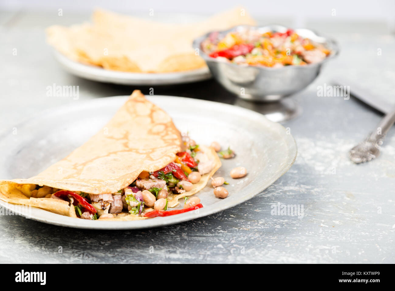 Savoury Buckwheat Pancake with White Beans, Red and Yellow Bell Pepper, Parsley and Chicken. Mexican Quesadilla. Stock Photo
