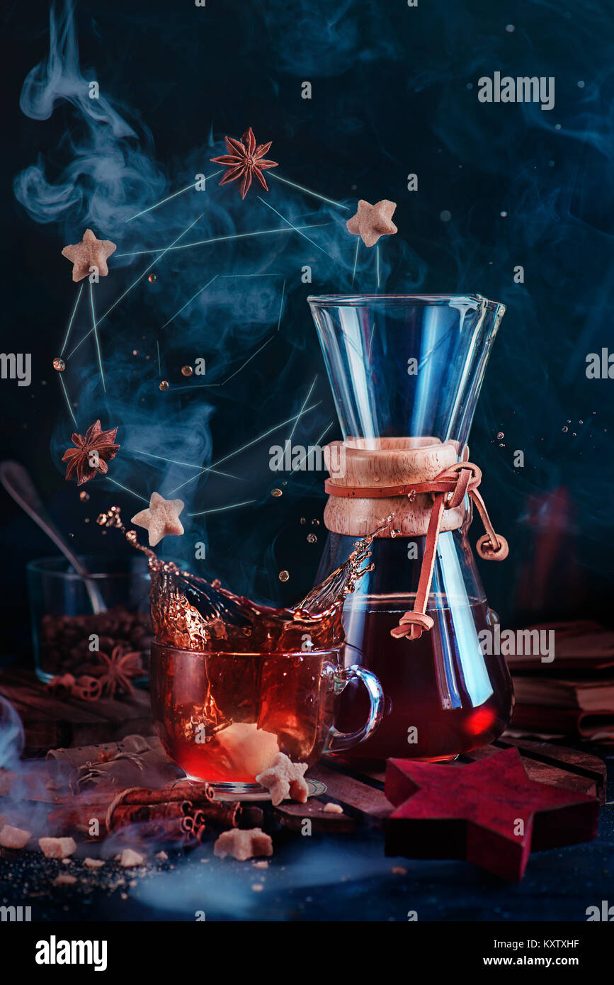 Glass coffee cup with a dynamic splash and rising steam with a donut constellation. Hourglass-shaped coffeemaker - Stock Image
