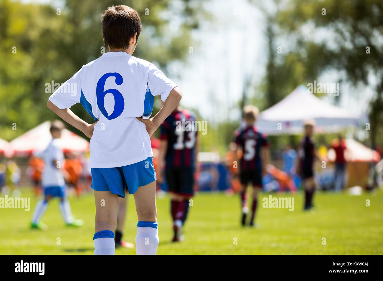 Kid Soccer Player. Young Professional Football Player. Young Boys Kicking Soccer Match - Stock Image