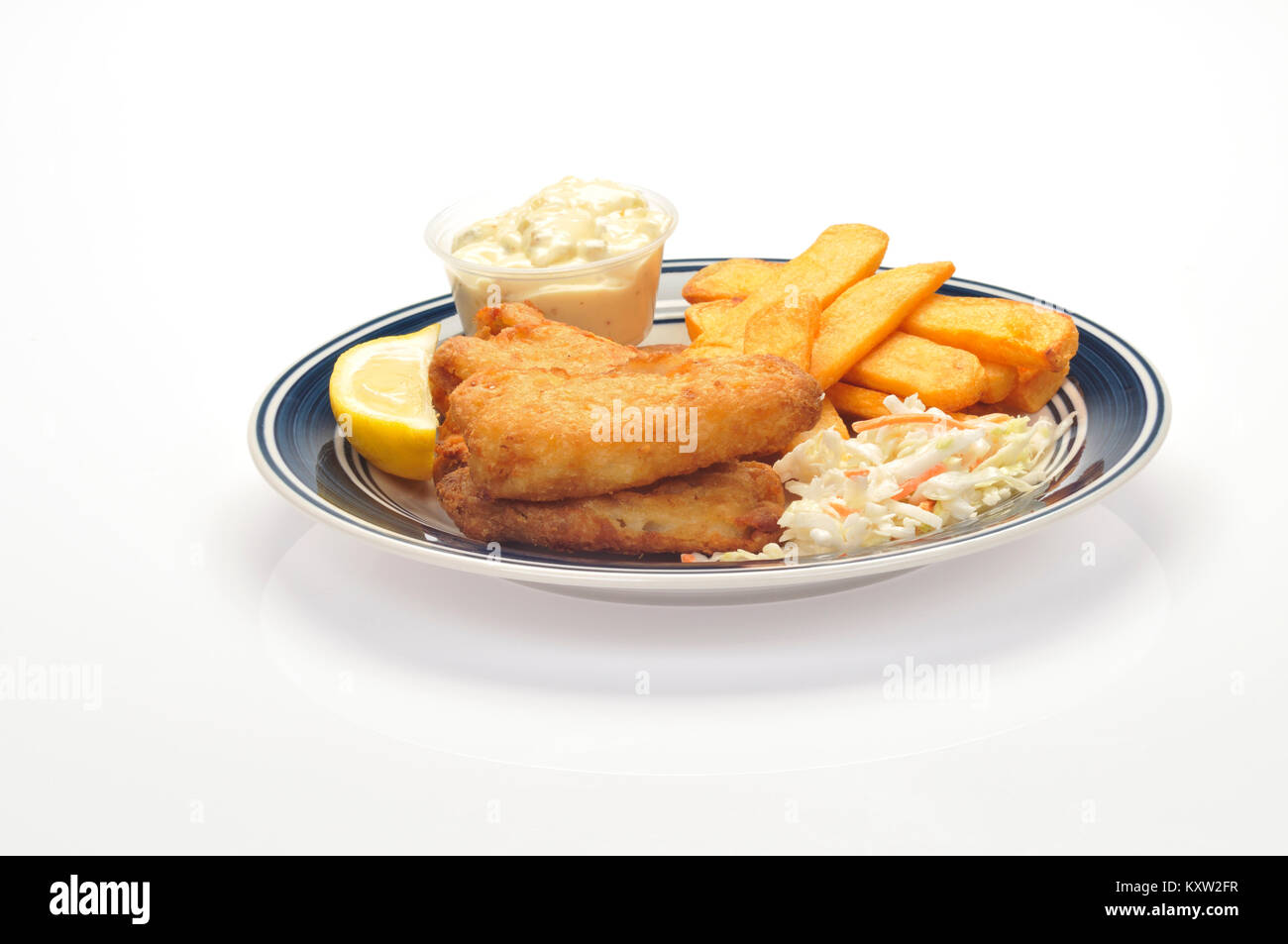 Fried fish and chips with a wedge of lemon, coleslaw and tartar sauce on blue and white plate on white background - Stock Image