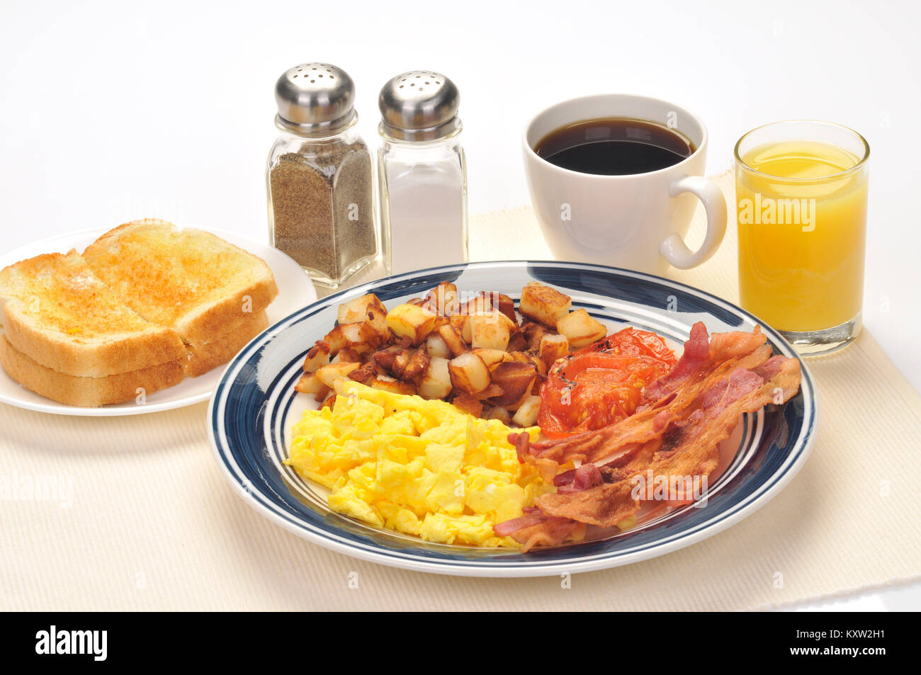 American blue plate breakfast special with scrambled eggs, hash brown potatoes, bacon, grilled tomatoes, buttered - Stock Image