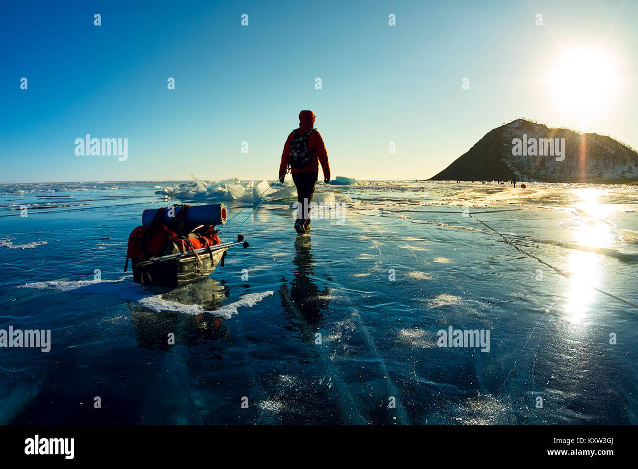 Woman with a sledge and trekking pole is on the ice of Lake Baikal. - Stock Image