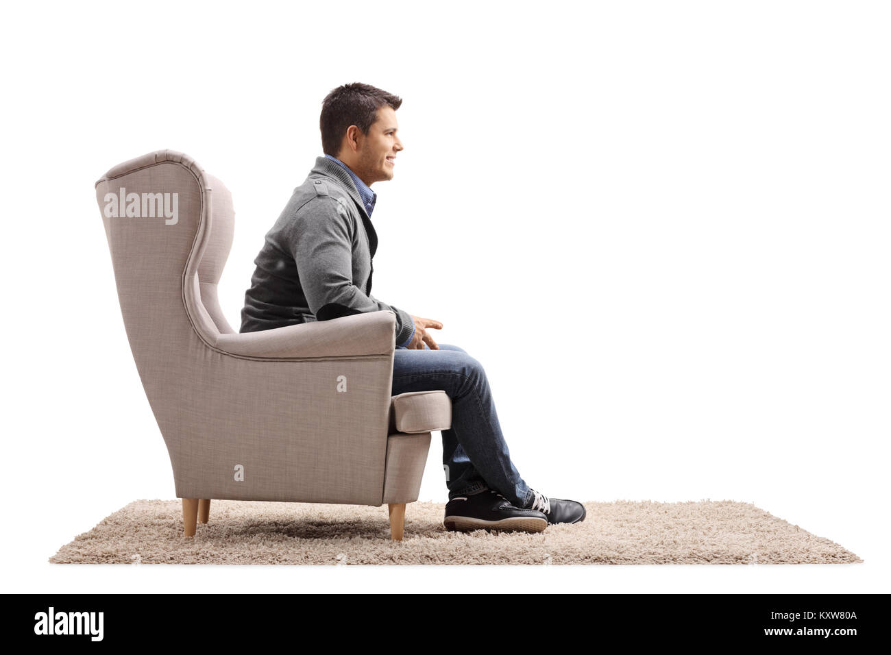 Man sitting in an armchair isolated on white background - Stock Image