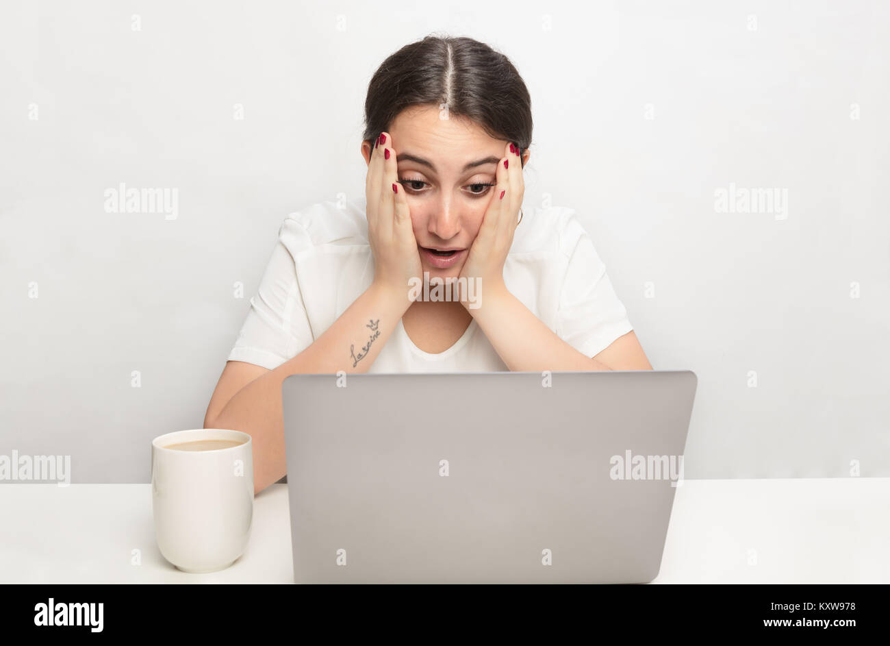 Young woman staring at a laptop in disbelief and shock resting her face on her hands as she stares at the screen - Stock Image