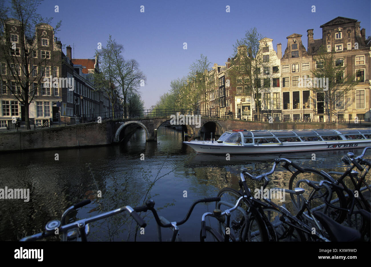 The Netherlands, Amsterdam, Canal called Herengracht.17th century. Bicycles. Canal or tour boat. - Stock Image