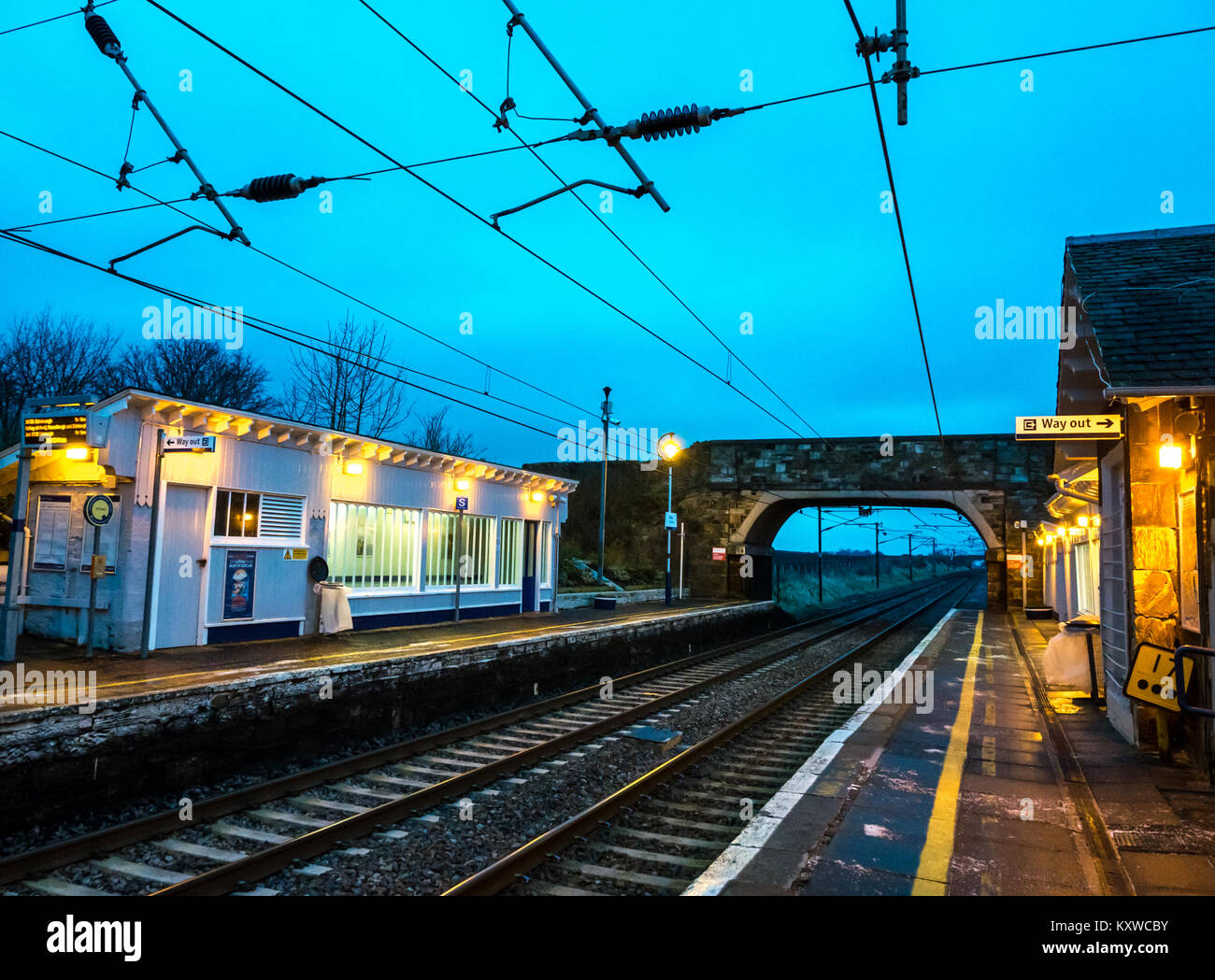 Drem Railway Station, East Lothian, Scotland, UK, at dusk with lights on and Way Out sign lit up - Stock Image