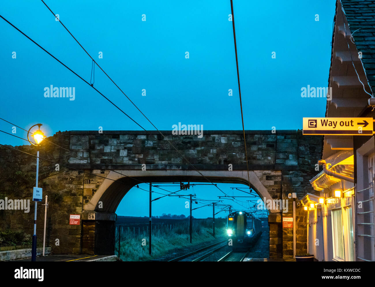 Drem Railway Station, East Lothian, Scotland, UK, at dusk with lights on and ScotRail train approaching under a - Stock Image