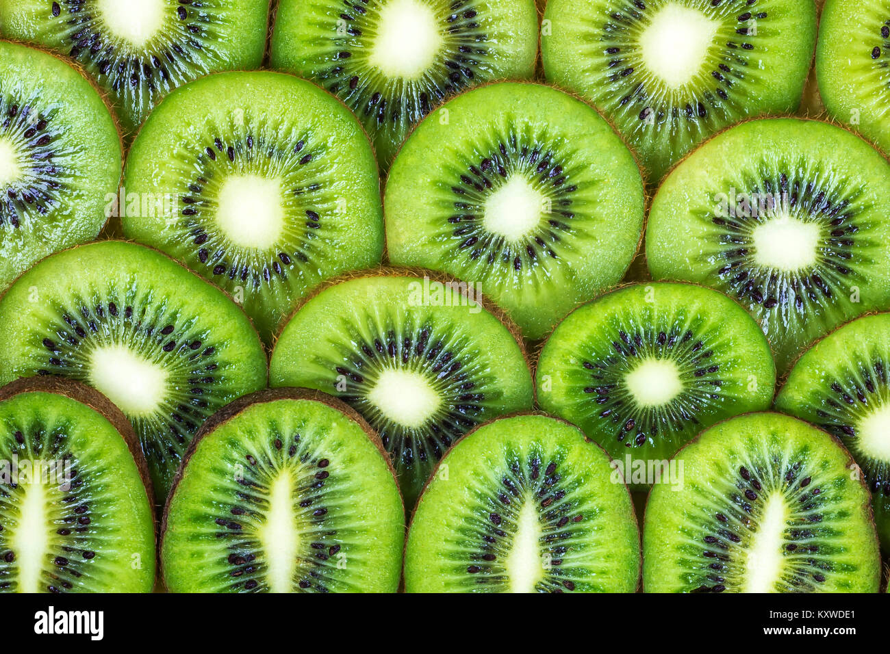 Slices of kiwi are on each other closeup around the image - Stock Image