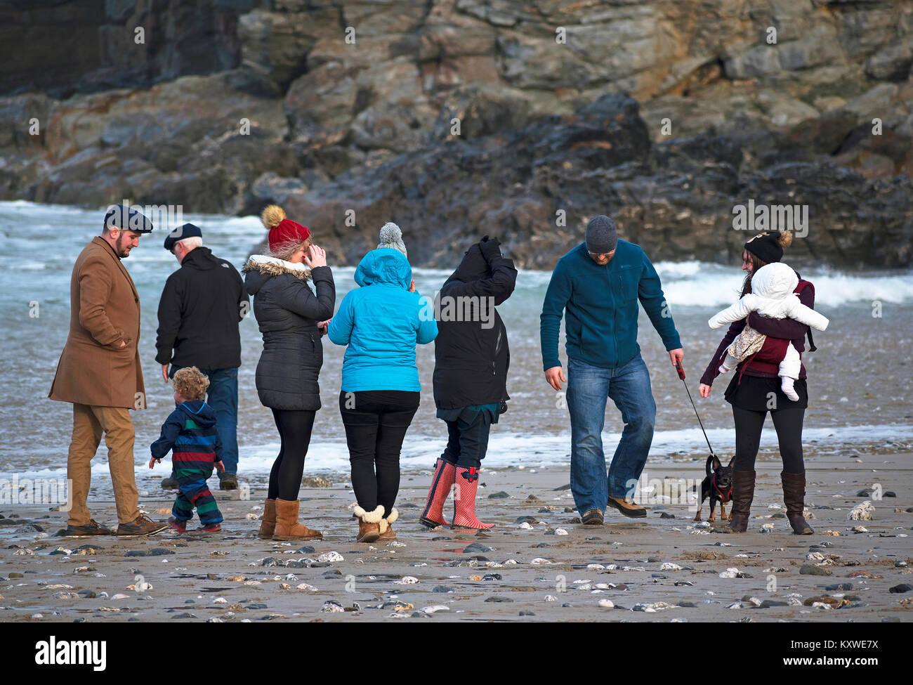 three generations of family having a winter walk on the beach at porthtowan in cornwall, uk. - Stock Image