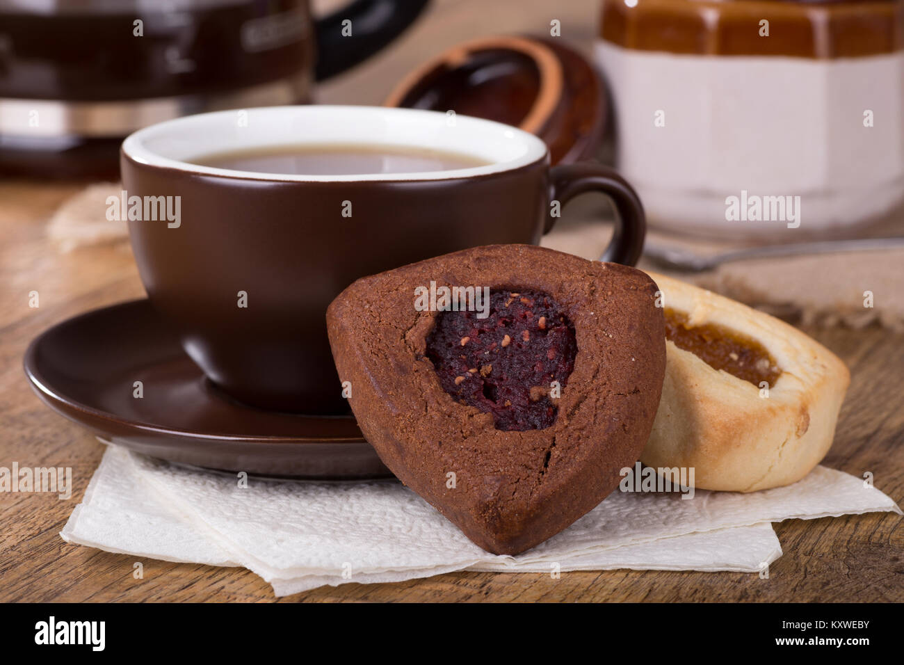 Raspberry and apricot filled hamantash cookies and cup of coffee - Stock Image