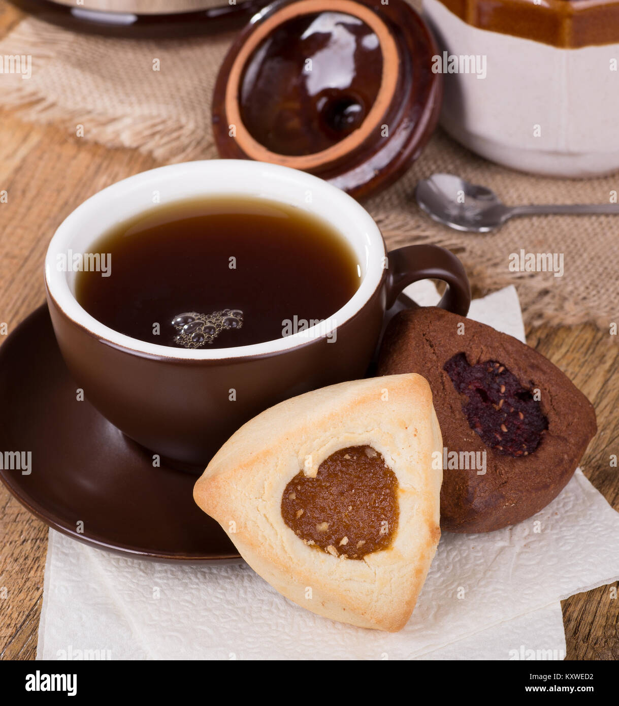 Apricot and raspberry filled hamantash cookies and cup of coffee - Stock Image