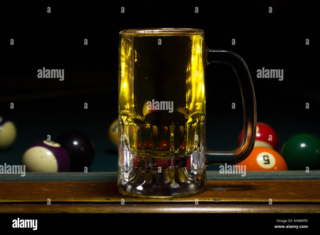 a cold mug with beer on a billard table with black background - Stock Image