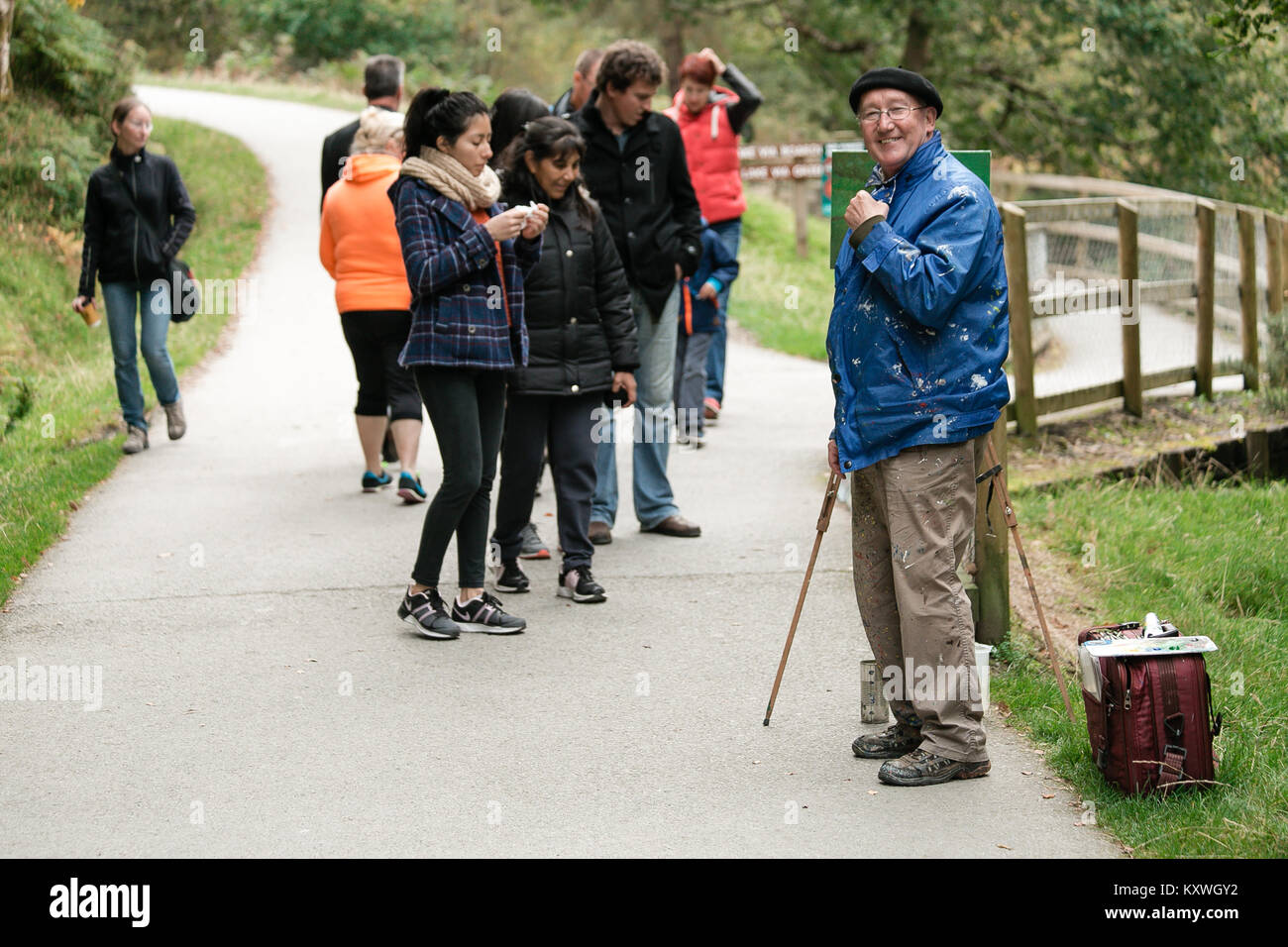 Artist painter painting the nature scenery in Glendalough Valley mesmerizing passing by tourists with his beautiful - Stock Image