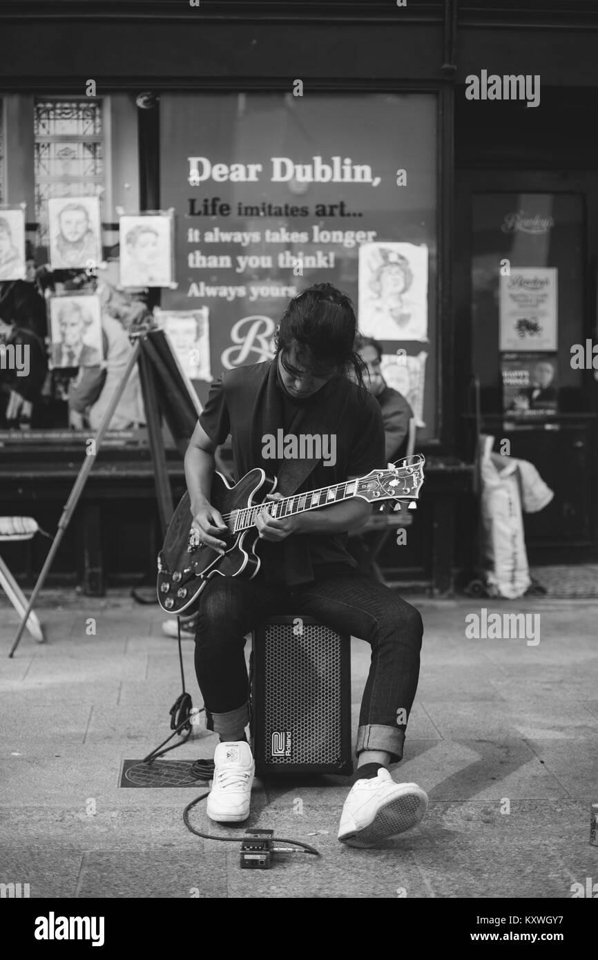 Man artist busking playing a Gibson guitar on Grafton Street in Dublin, Ireland - Stock Image