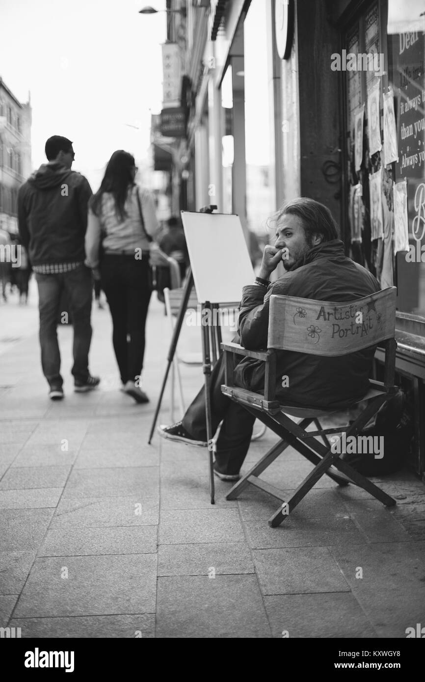 Male Artist painter specializing in sketching artistic portraits on Grafton Street waiting for customers. Dublin, - Stock Image