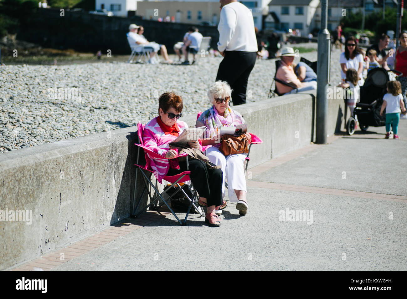 Two elderly ladies enjoying good weather reading newspapers on a promenade in Bray County Wicklow Ireland - Stock Image