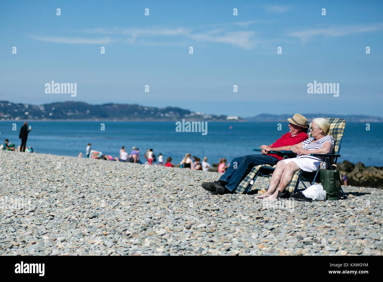 Elderly couple man and woman relaxing on a sunny summer day on a stone beach in Bray, County Wicklow, Ireland - Stock Image