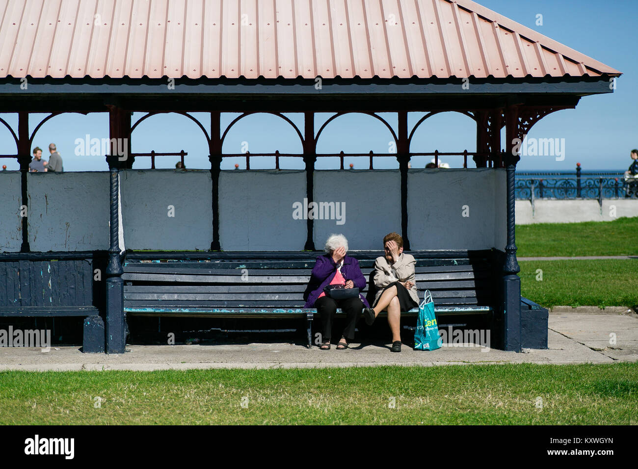 Two elderly women sitting in shelter on the bench and talking on Bray`s promenade in County Wicklow Ireland - Stock Image