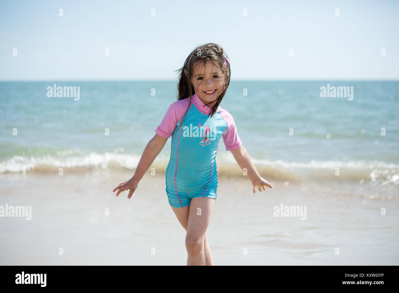 5 year old girl smiling enjoying sunny summer day on the sandy Brittas Bay Beach in County Wicklow, Ireland - Stock Image