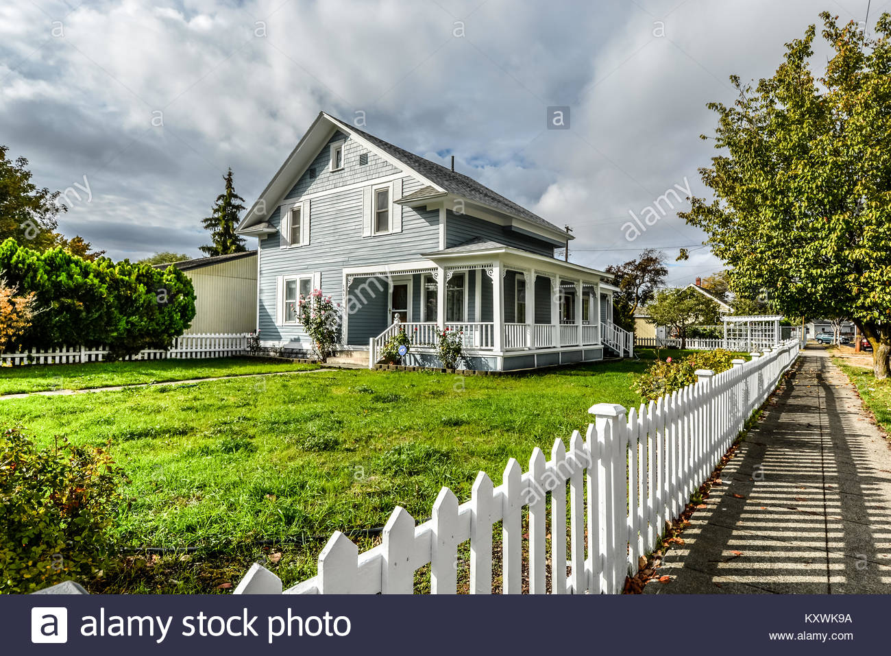 A cute victorian home with a white picket fence and large wraparound porch in the Pacific Northwest area of the - Stock Image