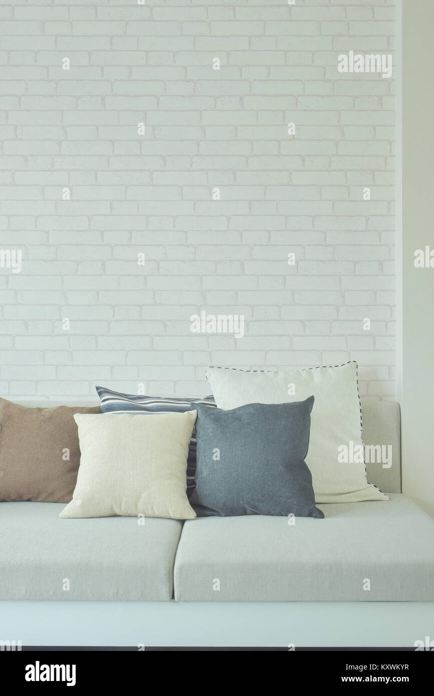Earth tone color pillows on sofa with white brick wall in background ...
