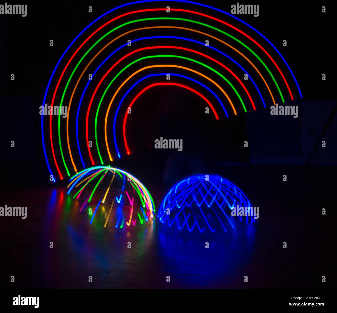 multi-coloured light trails patterns in shape of arc rainbow above multi-coloured and blue light domes - abstract Stock Photo