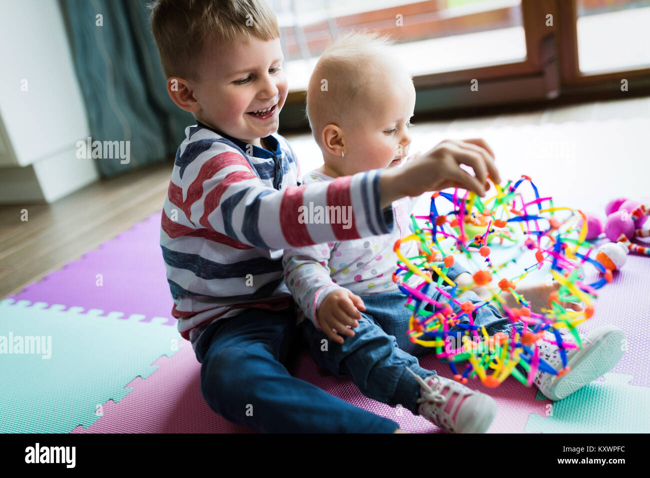 Cute little children playing while sitting on carpet Stock Photo