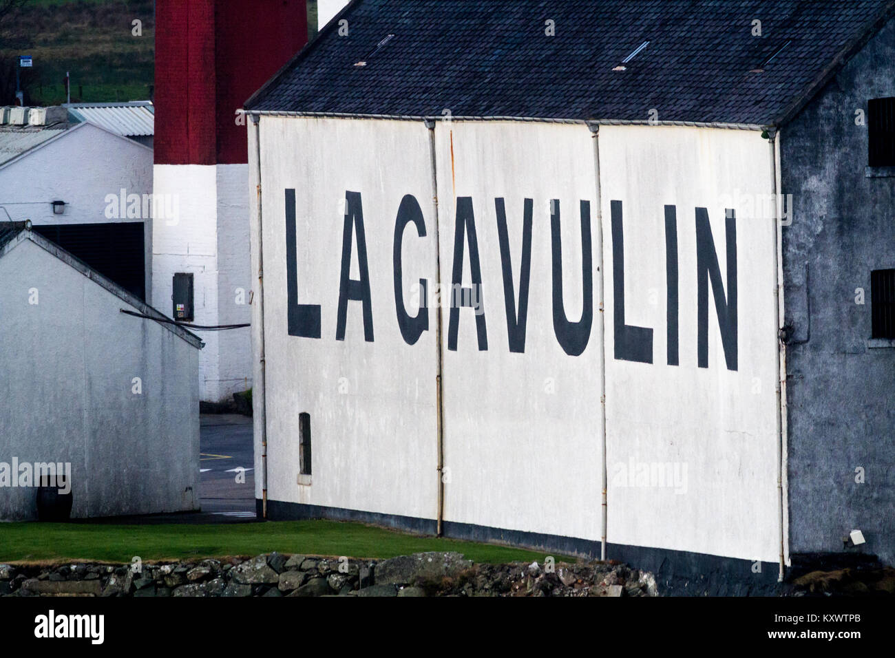 Close up of the outside of Lagavulin Whisky Distillery big black letters on whitewashed walls, Isle of Islay, Scotland - Stock Image