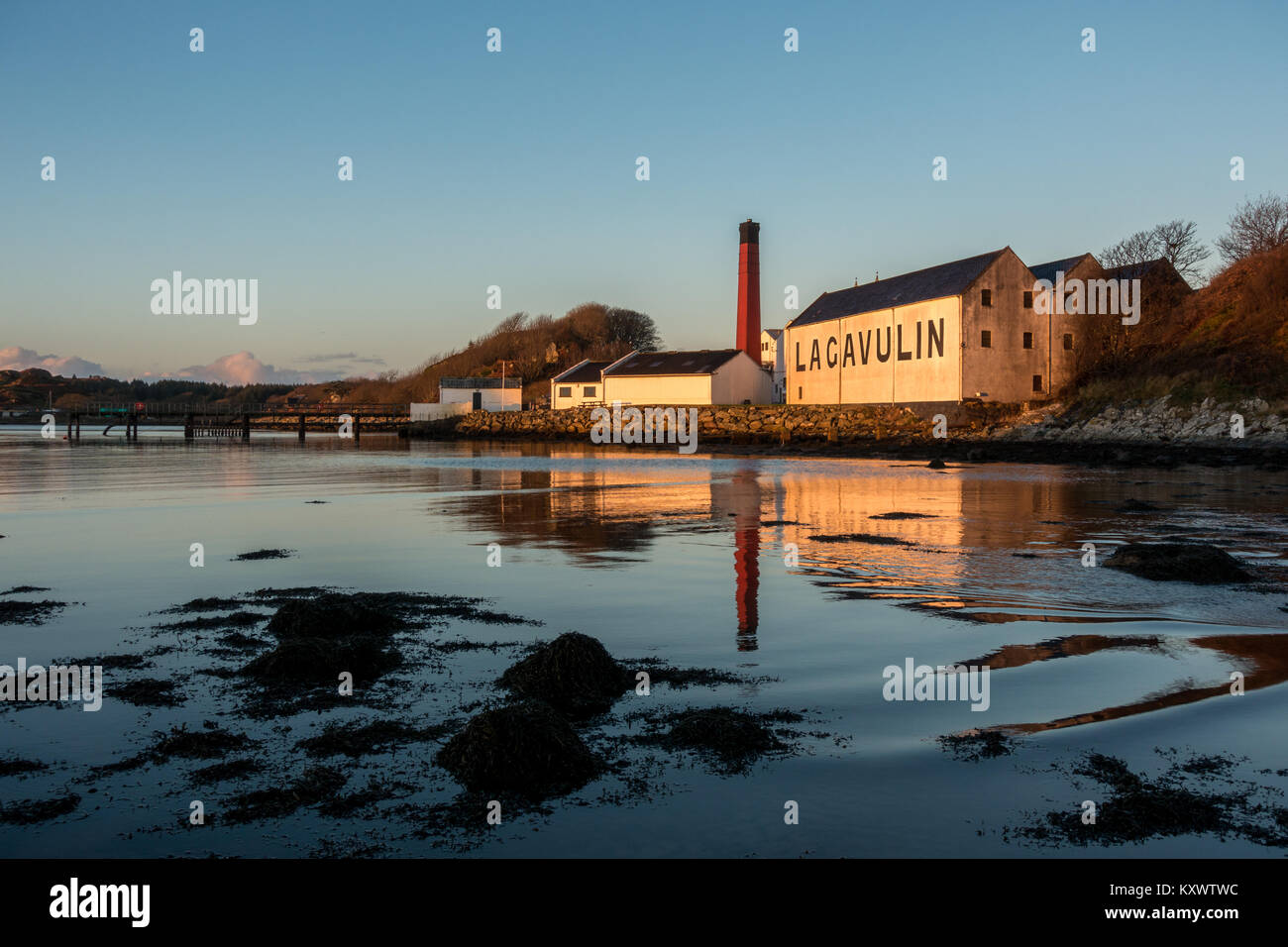 Lagavulin Whisky Distillery reflecting in the calm sea at dawn - blue sky, sunny day, Isle of Islay, Scotland - Stock Image