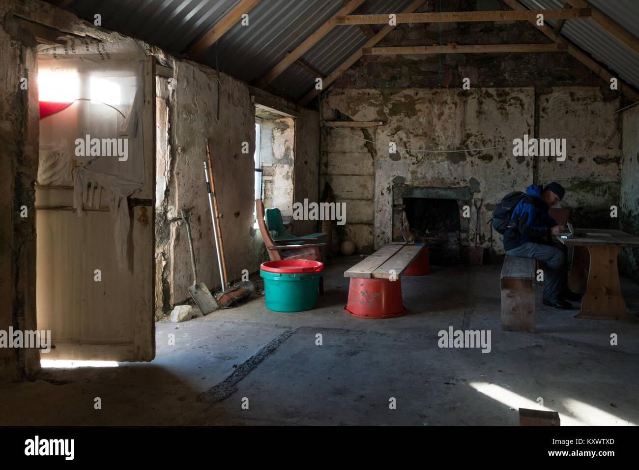 Inside Proaig Bothy with a walker sitting down, near Ardtalla, Isle of Islay, Scotland - Stock Image