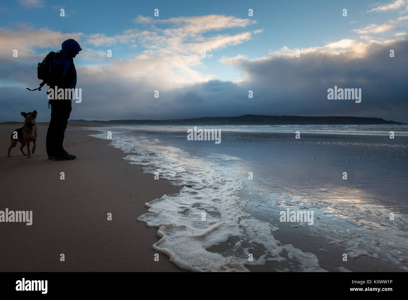Man walking dog on the Big Strand beach in beautiful evening light in winter, Isle of Islay, Scotland - Stock Image