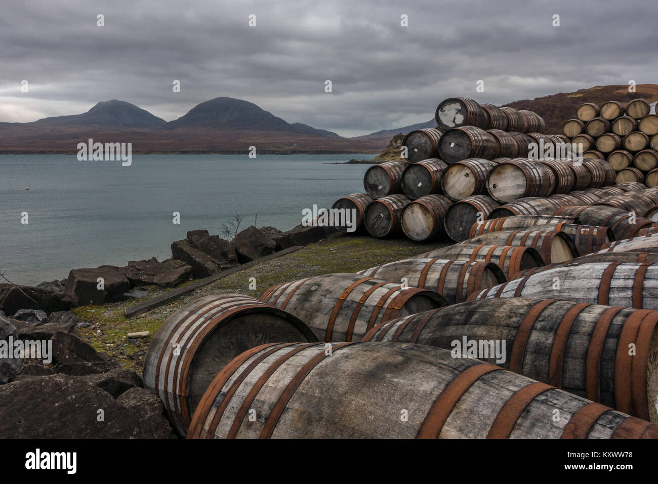 Scottish landscapes with whisky barrels stacked up at the Bunnahabhain Distillery and views of Isle of Jura, Isle - Stock Image