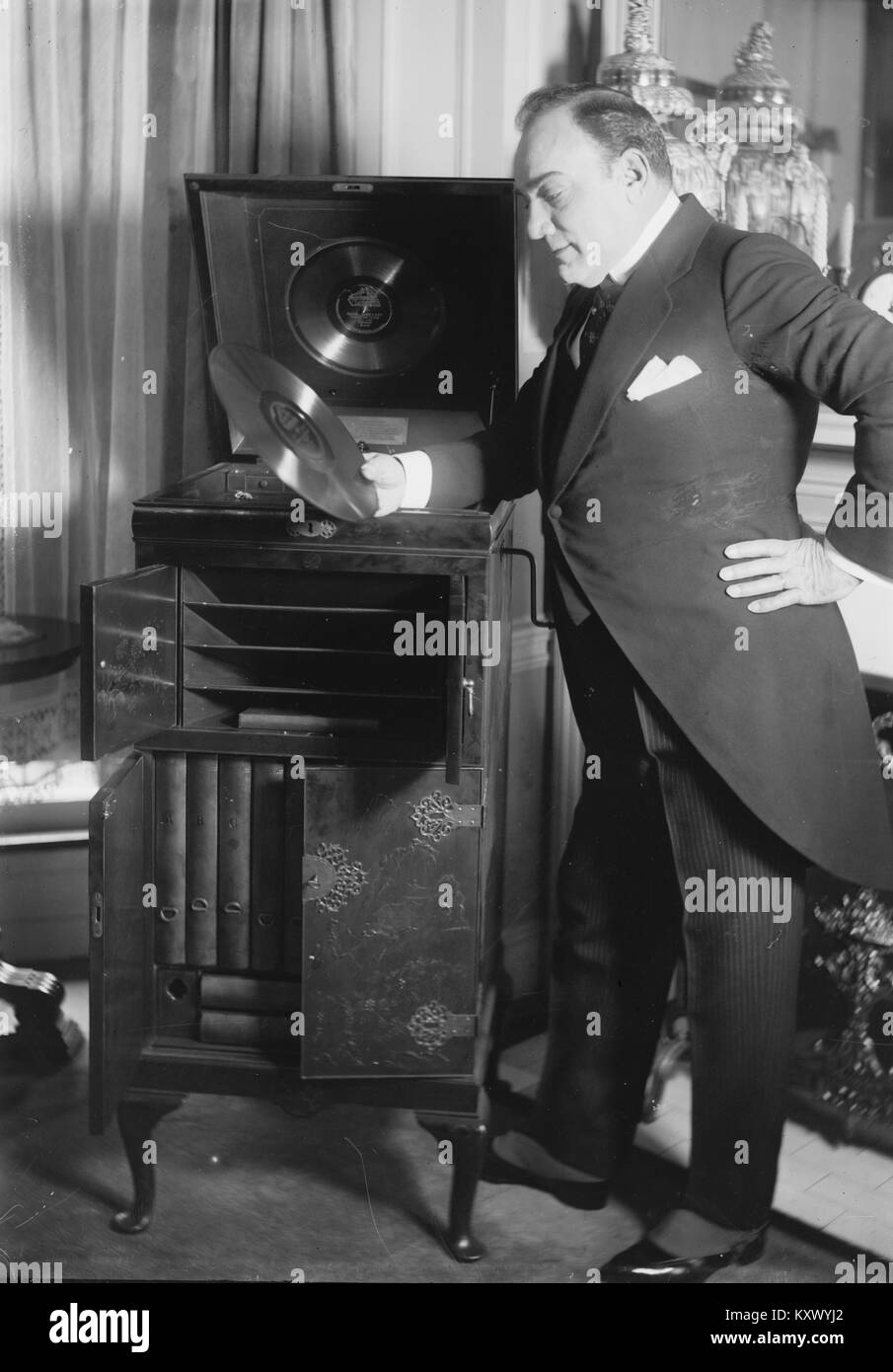Enrico Caruso Peruses a Disk if his Singing by a Phonograph - Stock Image