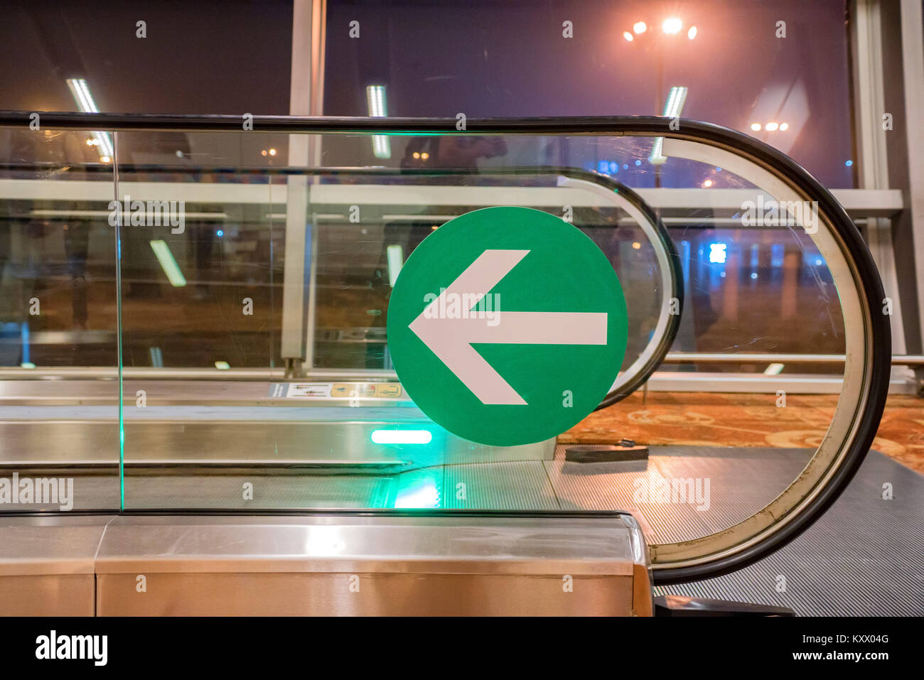 Green arrow sign on airport travelator - Stock Image