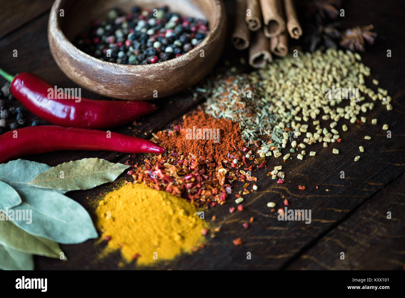 close up of pepper in bowl with scattered spices, laurel leaves, chili peppers on wooden tabletop - Stock Image