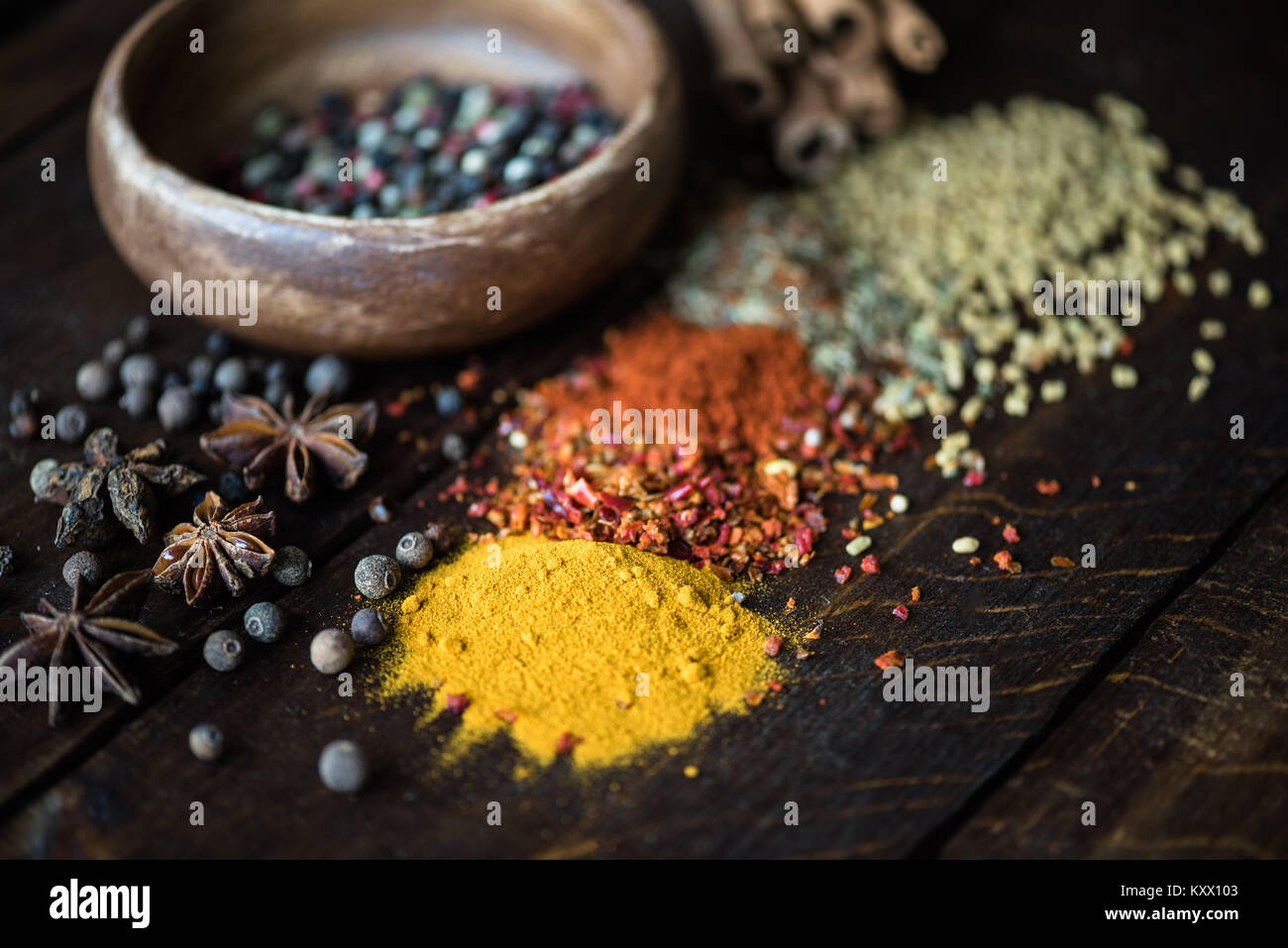 different kinds of pepper in bowl and spices with herbs scattered on wooden tabletop - Stock Image