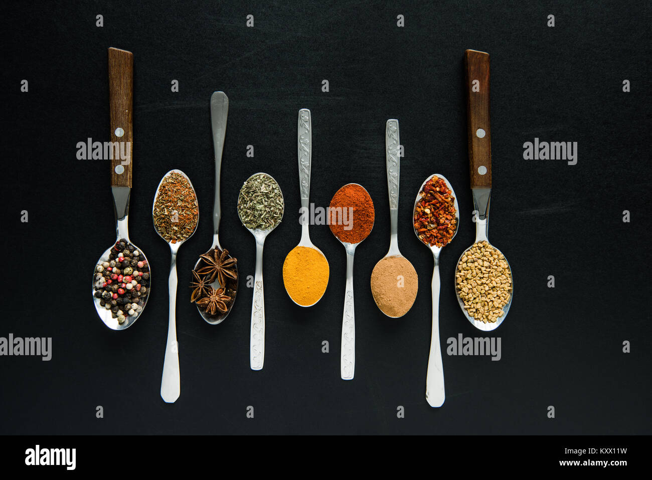 top view of various spices and herbs in metal spoons isolated on black - Stock Image